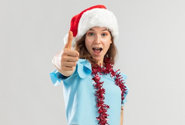 青いトップとサンタの帽子をかぶった若い女性が首に見掛け倒しをして幸せそうに見え、親指を立てて興奮している