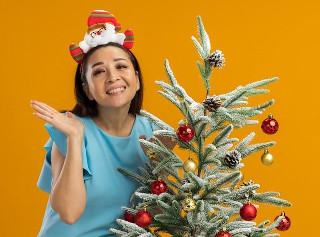 오렌지 벽 위에 서 행복하고 쾌활한 웃는 크리스마스 트리를 장식하는 재미있는 크리스마스 테두리를 입고 파란색 상단에 젊은 여자