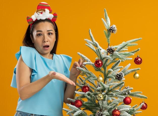 面白いクリスマスの縁を身に着けている青いトップの若い女性は、オレンジ色の背景の上に立って不満で腕を上げて混乱しているように見えるクリスマスツリーを飾る