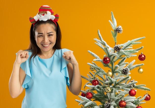 頭に面白いクリスマスの縁を身に着けている青いトップの若い女性は、オレンジ色の背景の上のクリスマスツリーの横に立って幸せで興奮した拳を握りしめます