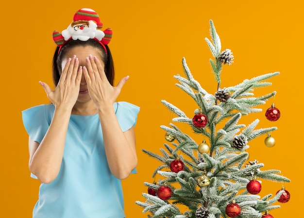 オレンジ色の壁の上のクリスマスツリーの横に立っている手で目を覆う頭に面白いクリスマスの縁を身に着けている青いトップの若い女性