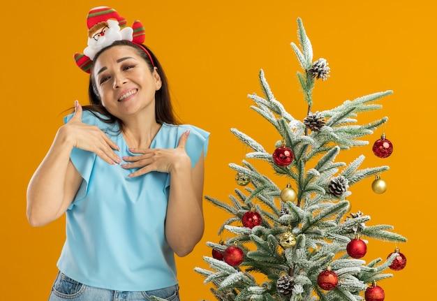 頭に面白いクリスマスの縁を身に着けている青いトップの若い女性幸せで前向きな彼女の胸に手をつないでオレンジ色の背景の上のクリスマスツリーの横に立って感謝を感じています