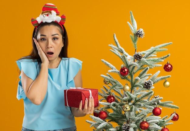 오렌지 배경 위에 크리스마스 트리 옆에 서있는 그녀의 뺨에 손으로 놀란 현재 카메라를보고 들고 머리에 재미있는 크리스마스 테두리를 입고 파란색 상단에 젊은 여자