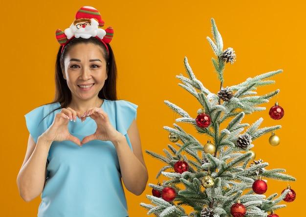 オレンジ色の背景の上のクリスマスツリーの横に立っている指でハートジェスチャーを作る頭に面白いクリスマスの縁を身に着けている青いトップの若い女性