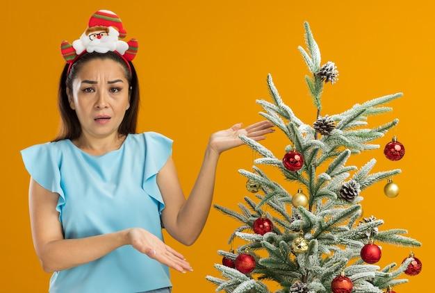 오렌지 배경 위에 불만과 분노에 손을 올리는 혼란 찾고 크리스마스 트리 옆에 서있는 머리에 재미있는 크리스마스 테두리를 입고 파란색 상단에 젊은 여자