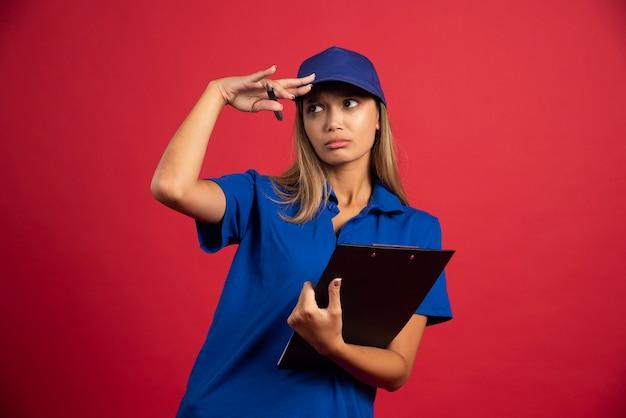 鉛筆でクリップボードを保持している青い制服を着た若い女性。