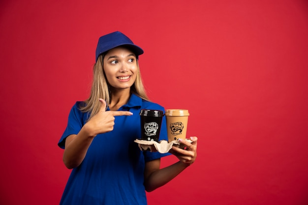 2つのカップのカートンを指している青い制服を着た若い女性。