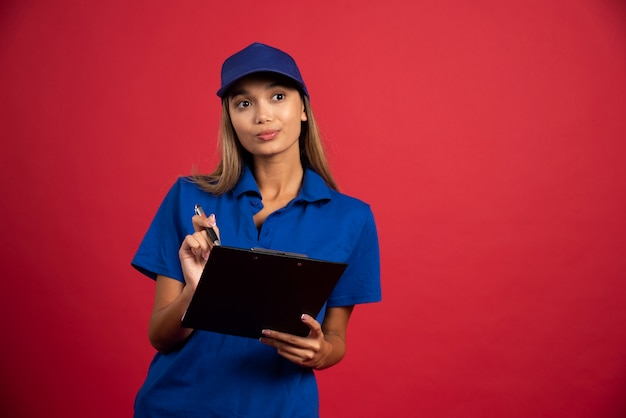 Молодая женщина в синей форме позирует с буфером обмена и карандашом.
