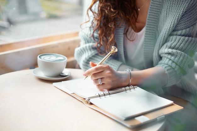 コーヒーショップの大きな窓の近くに座って、青いラテのカップでクリスマスの買い物リストを書いている青い暖かいセーターの若い女性。クリスマス休暇の計画。コンセプトの整理と計画。