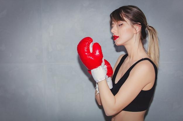 灰色の背景にボクシンググローブの若い女性。 90年代の懐中電灯スタイル