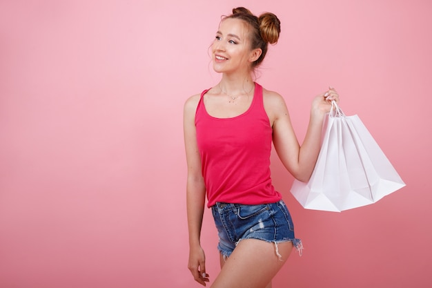 종이 흰색 봉투와 밝은 옷에 젊은 여자. 쇼핑 프리미엄 사진