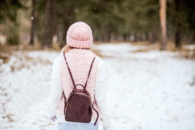 冬の雪に覆われた森の中を歩くバックパックと明るいピンクの服を着た若い女性。後ろからの眺め