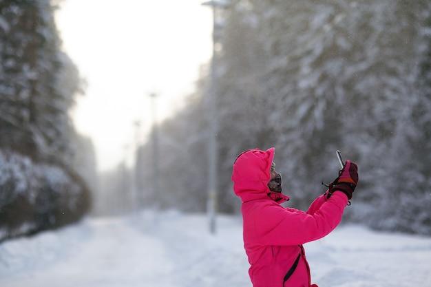 凍るような寒い日に屋外で自分撮りを作る明るいピンクのスポーティーな冬の服を着た若い女性。コピースペース