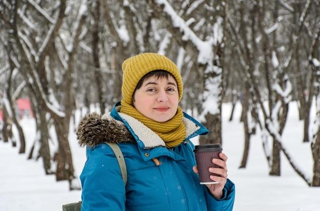 明るい冬の帽子とジャケットを着た若い女性がウィンターパークを散歩し、紙コップのコーヒーを持って持ち帰ります。
