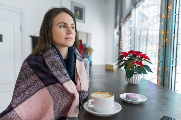 暖かい毛布で温かい飲み物のカップを持つカフェで若い女性