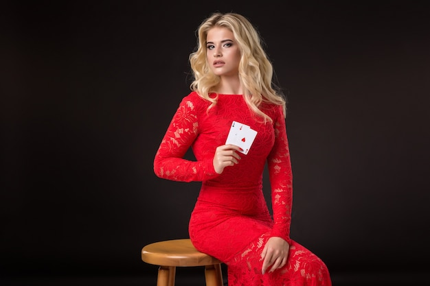 黒の背景にカードを持つカジノの若い女性。ポーカー
