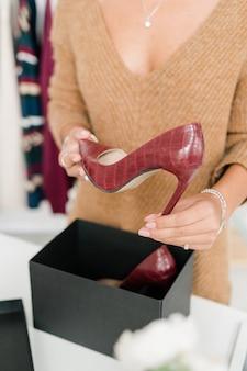 オープンブラックボックスにかかとの高い栗色の革の靴を保持しているカジュアルなベージュウールプルオーバーの若い女性