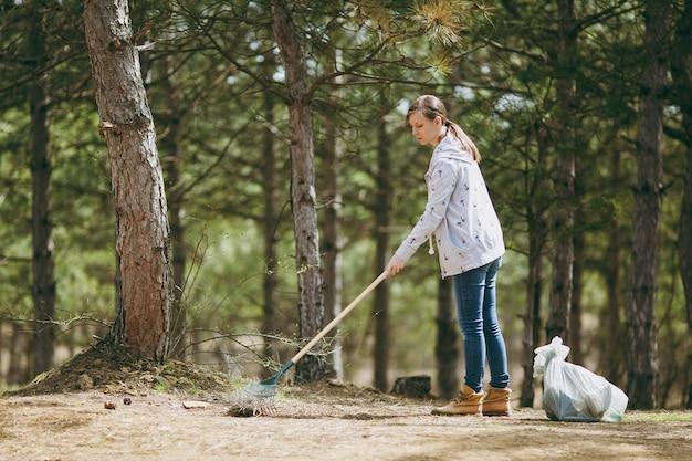 Молодая женщина в повседневной уборке одежды и использовании граблей для сбора мусора возле мешков для мусора в парке или лесу. проблема загрязнения окружающей среды. остановить мусор природы, концепция защиты окружающей среды.