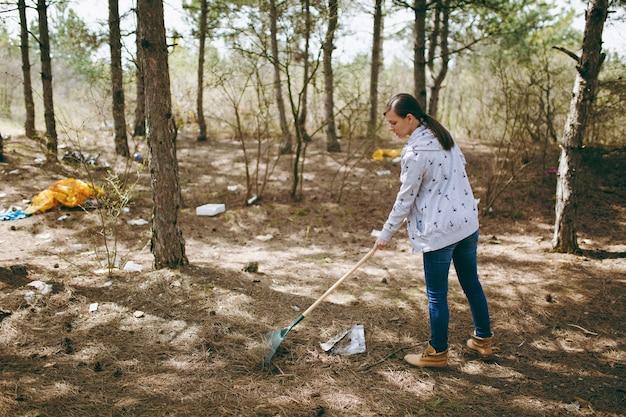 흩어져 있는 공원이나 숲에서 쓰레기 수거를 위해 갈퀴를 사용하여 쓰레기를 청소하는 캐주얼 옷을 입은 젊은 여성. 환경오염 문제
