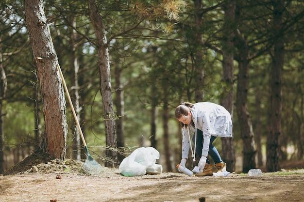 Молодая женщина в повседневной одежде, перчатках, убирающих мусор в мешки для мусора в парке или лесу на зеленой стене