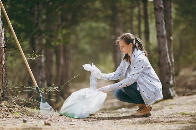 Молодая женщина в повседневной одежде, перчатках, убирающих мусор в мешки для мусора в парке или лесу
