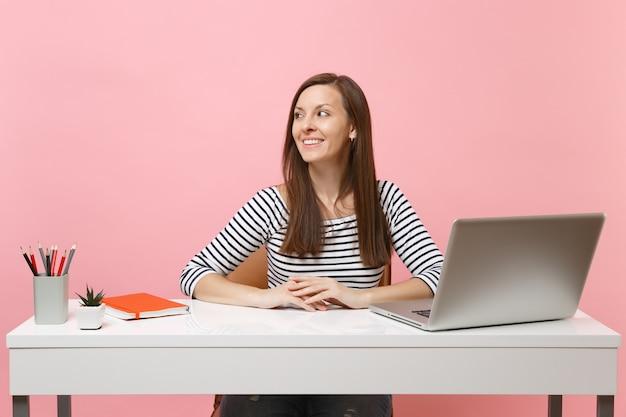 캐주얼 옷을 입은 젊은 여성이 옆자리에 앉아 현대적인 pc 노트북이 있는 흰색 책상에서 일합니다.