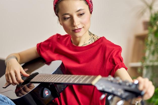 집에서 기타를 치는 동안 집중해 보이는 캐주얼 옷을 입은 젊은 여성