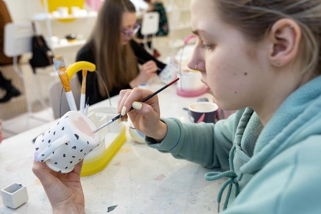 평상복을 입은 젊은 여성이 사진에 초점을 맞춘 도자기 워크숍에서 세라믹 컵 뒷면에 분홍색 하트를 칠한다