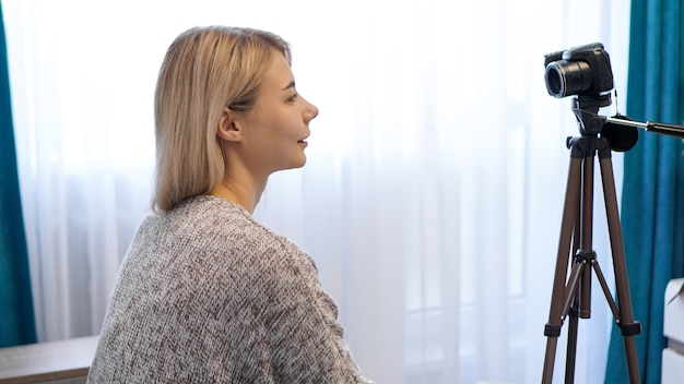 カジュアルな服装の若い女性が三脚のカメラに自分自身を記録します。側面図。自宅でビデオを録画する陽気な女性ブロガー