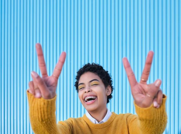 승리 기호를 만드는 그녀의 손가락을 보여주는 카메라를보고 웃 고 캐주얼 옷에 젊은 여자.