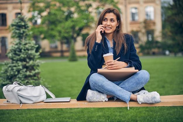 책과 커피와 함께 벤치에 앉아있는 동안 전화로 얘기 캐주얼 옷에 젊은 여자