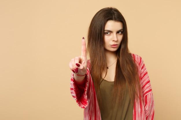 カジュアルな服装の若い女性は、パステルベージュの背景に分離されたフローティング仮想画面を指して、ボタンのプッシュクリックのようなものに触れます。人々の感情のライフスタイルの概念。コピースペースをモックアップします。