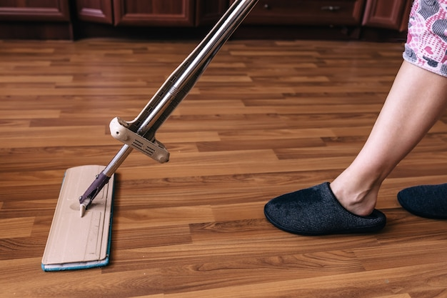 Молодая женщина в повседневной одежде стирает деревянный ламинатный пол
