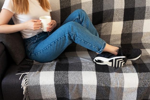 室内の白いカップが付いているソファーのカジュアル衣料品緩和の若い女性。家で休む、ライフスタイル