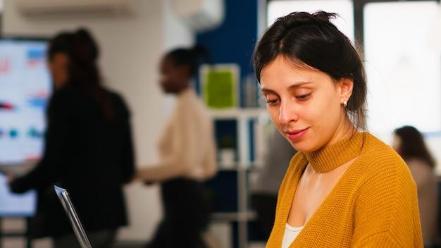 다양한 팀이 현대 사무실에서 통계 데이터를 분석하는 동안 바쁜 금융 신생 기업의 책상에 앉아 노트북에서 일하는 캐주얼 복장의 젊은 여성. 작업에 집중하는 다민족 팀