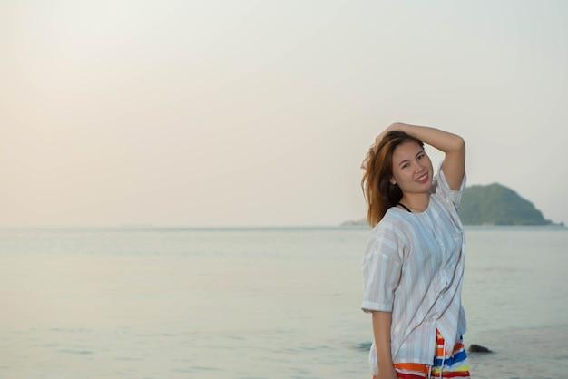 Молодая женщина в повседневном платье и стоит на пляже