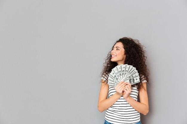 Молодая женщина в повседневной одежде держит веер 100 долларовых банкнот в руках, глядя в сторону с широкой улыбкой, радуясь над серой стеной