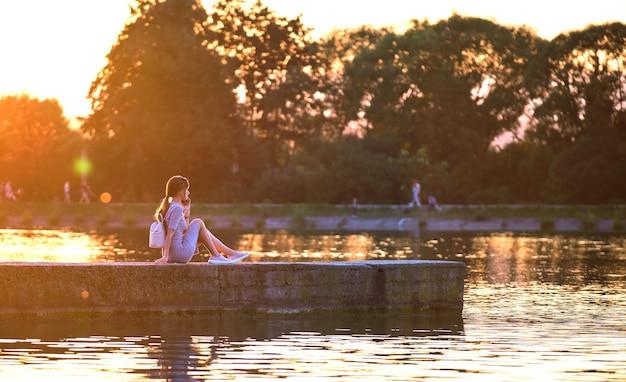 Молодая женщина в повседневной одежде расслабляющий на берегу озера в теплый вечер. летние каникулы и путешествия концепции.