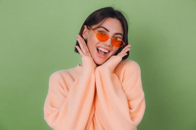 Молодая женщина в повседневном персиковом и оранжевом свитере для очков изолирована на зеленой оливковой стене взволнована, держа рот открытым, разводя руками