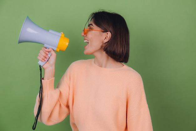 緑のオリーブの壁に分離されたカジュアルな桃とオレンジ色の眼鏡のセーターの若い女性は、メガホンのコピースペースで幸せな叫び声を上げる