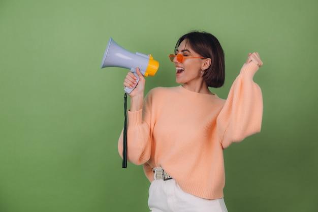 Молодая женщина в повседневном персиковом и оранжевом свитере для очков изолирована на зеленой оливковой стене, счастливая кричит в копировальном пространстве мегафона