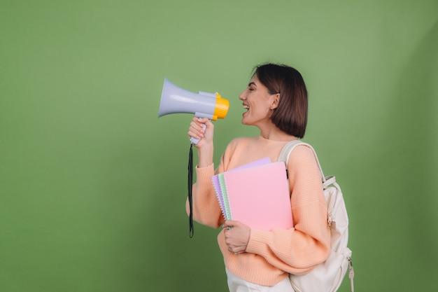 캐주얼 복숭아 스웨터와 배낭에 젊은 여자는 녹색 올리브 색 벽에 고립