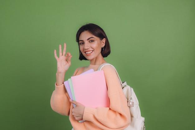 Молодая женщина в повседневном персиковом свитере и рюкзаке изолирована на стене зеленого оливкового цвета