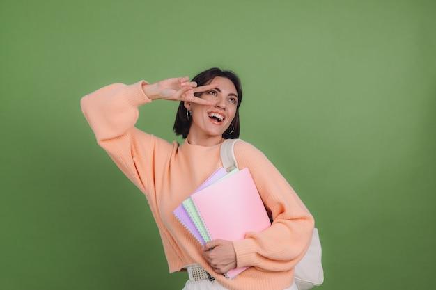 緑のオリーブ色の壁に分離されたカジュアルな桃のセーターとバックパックの若い女性