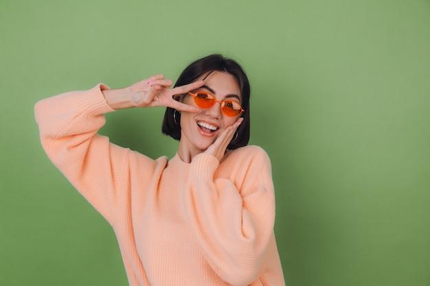 Молодая женщина в повседневном персиковом свитере и оранжевых очках изолирована на зеленой оливковой стене, смешно делает победный жест копией пространства