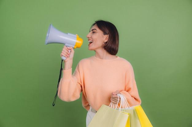 녹색 올리브 색 벽에 고립 된 캐주얼 복숭아 스웨터에 젊은 여자 쇼핑 가방을 들고 확성기에 소리, 할인 판매 촉진을 발표 프리미엄 사진
