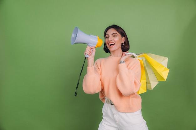 녹색 올리브 색 벽에 고립 된 캐주얼 복숭아 스웨터에 젊은 여자 쇼핑 가방을 들고 확성기에 소리, 할인 판매 촉진을 발표