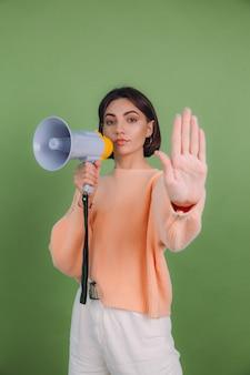 緑のオリーブ色の壁に分離されたカジュアルな桃のセーターの若い女性。メガホンが手のひらで歌うのをやめることに不幸な深刻
