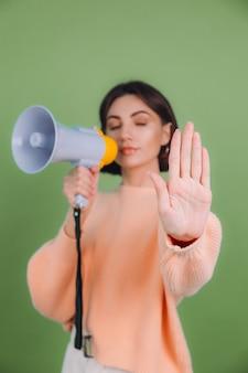 녹색 올리브 색 벽에 고립 된 캐주얼 복숭아 스웨터에 젊은 여자. 확성기가 손바닥으로 노래를 멈추는 불행한 심각한