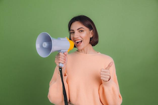 녹색 올리브 색 벽에 고립 된 캐주얼 복숭아 스웨터에 젊은 여자